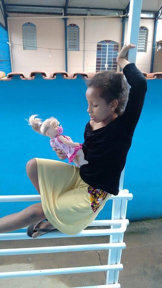 Nina canta con su muñeca frente al consultorio