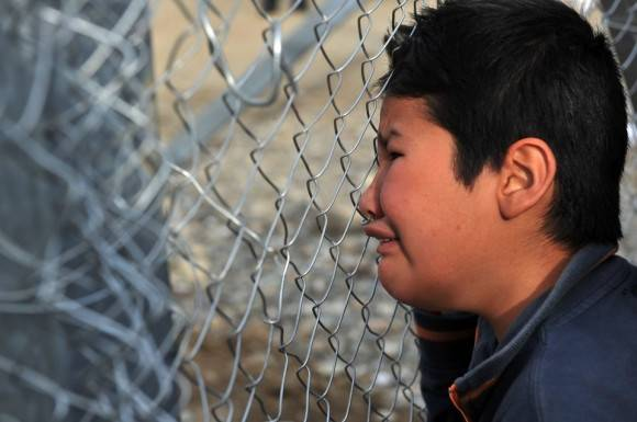A young boy from Afghanistan cries as he places his face against the fence at the Greece-Macedonia border during a demonstration near the village of Idomeni, northern Greece, on February 22, 2016, against Macedonia's refusal to allow Afghans to pass the border.  Greece said on February 22 that it was taking action to persuade Macedonia to take in Afghan migrants as thousands remained stranded at the border and the main port in Athens. About 5,000 refugees and migrants are stuck at the border with Macedonia after the neighbouring non-EU state on February 21 refused to allow passage to Afghans, police said. / AFP / SAKIS MITROLIDIS        (Photo credit should read SAKIS MITROLIDIS/AFP/Getty Images)