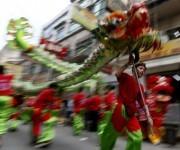Un dragón verde se extiende danzando por la calle y visita los establecimientos comerciales en Manila, en Filipinas. (Foto: AP)
