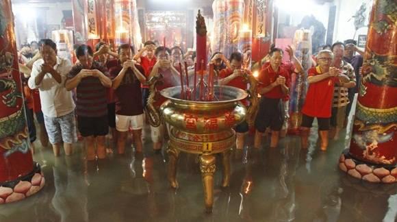 Indonesios de origen chino oran en un templo inundado después de una fuerte lluvia en Java Oriental, Indonesia. (Foto: AP)