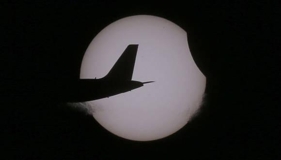La cola de un avión de pasajeros sobrevuela el cielo de la ciudad filipina de Taguig durante el eclipse solar. Foto: Bullit Marquez.