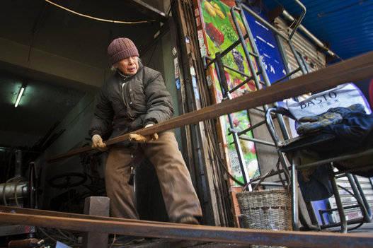 Liu Shujian, una señora de 90 años de edad, continúa su trabajo de soldadura eléctrica en la calle Wanshousi el 5 de diciembre de 2014 en Shenyang, provincia de Liaoning, en China. Foto: Getty Images.
