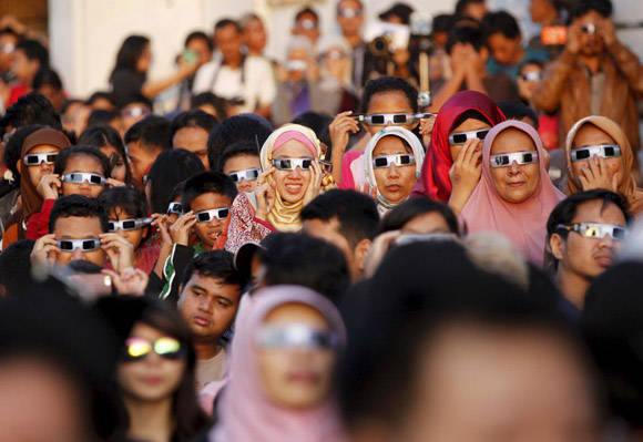 Un grupo de personas contemplan el eclipse solar en Jakarta (Indonesia). Foto: Garry Lotulung/Reuters.