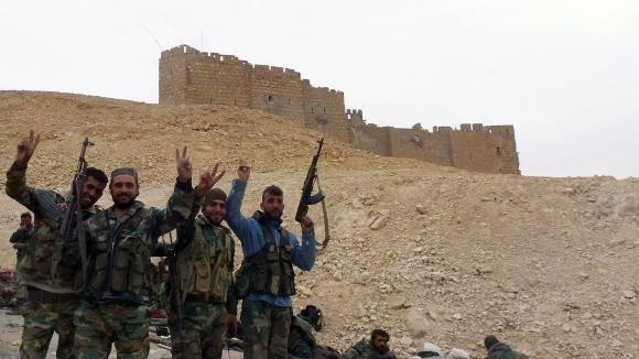 Fuerzas progubernamentales sirias hacen el signo de la victoria cerca de la ciudadela de Palmira. Foto: AFP.