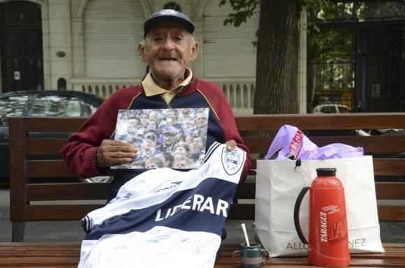 Ismael con su foto en la cancha del Lobo, y un obsequio especial de Germán, alguien que conoció su historia y le llevó una camiseta firmada por todo el plantel de Gimnasia. Foto: Kaloian.
