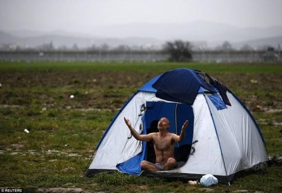 Hombre reza en su casa de campaña. Foto: Reuters.