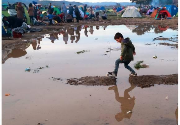 Niño refugiado juega en medio del fango. Foto: AP.