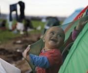 Niño refugiado sonríe en casa de campaña. Foto: Reuters.