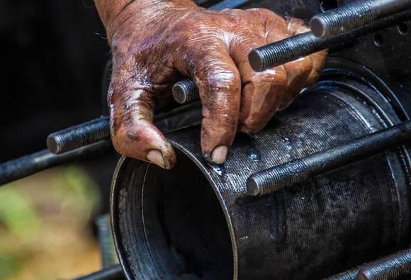 """Camino a Pinar del Río, en ambiente de Festival del Habano, sentí unos ruidos un poco alejados del escenario de los tabaqueros. Encontré estos dos mecánicos  """"fajados"""" con el motor de un tractor,  a la sombra de un árbol. Foto: Ismael Francisco/ Cubadebate"""