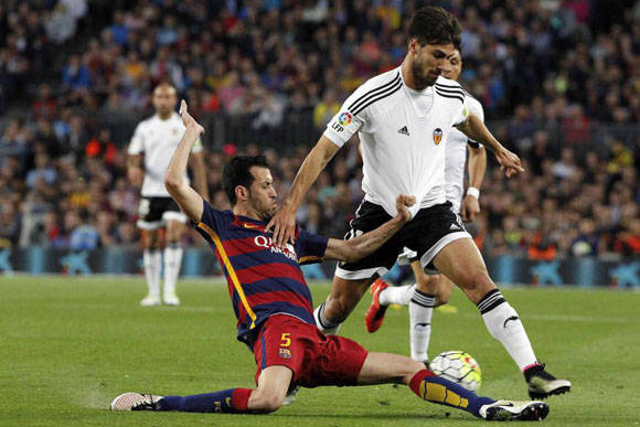 El centrocampista del Barcelona Sergio Busquets lucha el balón con el portugués André Gomes, del Valencia. Foto: EFE.