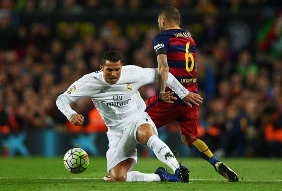 Cristiano Ronaldo del Real Madrid CF es derribado por Daniel Alves del FC Barcelona durante el partido en el Camp Nou. Foto: Getty Images.
