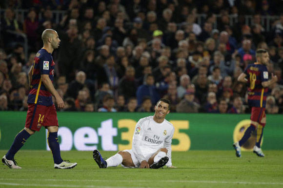 Cristiano Ronaldo, se sienta en el suelo durante el partido de fútbol entre el Barcelona y Real Madrid, en el estadio Camp Nou. Foto: AP.