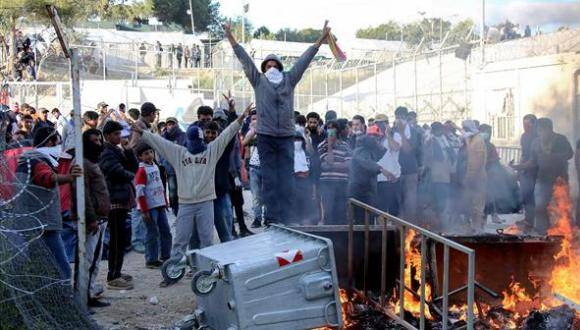 Los migrantes realizan un signo de la victoria que queman contenedores de basura en el centro de detención de migrantes Moria en la isla griega de Lesbos. Foto: AP.