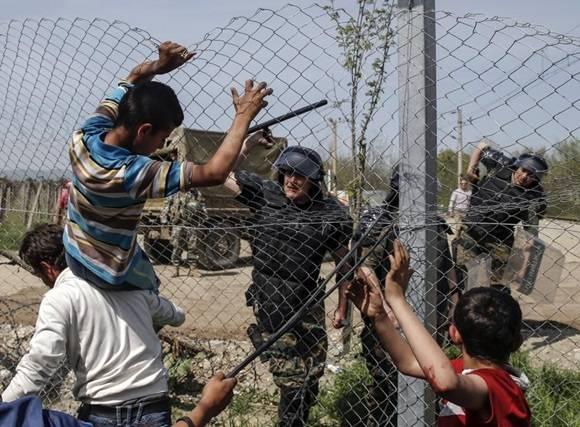 Un policía macedonio amenaza a los inmigrantes en Idomeni. Foto: Reuters.