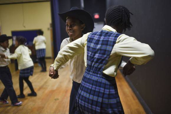 Jackson Adams, de 13 años, baila con Lindsay Smith, de 12, durante uno de muchos ensayos que los estudiantes han realizado antes de su viaje. Foto: Michael Robinson Chavez / The Washington Post