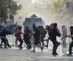 Barricadas incendiarias y la intervención de carros lanza agua de la policía tuvieron lugar en distintos puntos de la manifestación. Foto: AP
