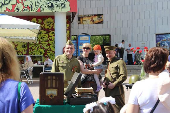 Las personas se hacen fotos al lado de soldados ataviados con los uniformes militares que vistieron los soviéticos en la ll Guerra Mundial mientras se escuchan melodías patrióticas en aparatos de música originales de aquella época.