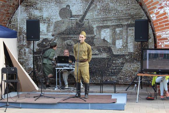 Un joven vestido de soldado soviético recita poesía escrita en la trinchera por un héroe caído en combate.