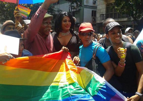 Wilber Pérez (Chacón, izq.) y Omar Franco (Ruperto, der.) sostienen una bandera con los colores identitarios de la comunidad LGTBI. Foto tomada del perfil de Facebook de Yunel Labacena.