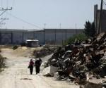 Mujeres palestinas caminan por las zonas donde se militantes de Hamas fueron localizados cerca de la frontera con Israel, al este de la ciudad de Gaza. Foto: AFP.