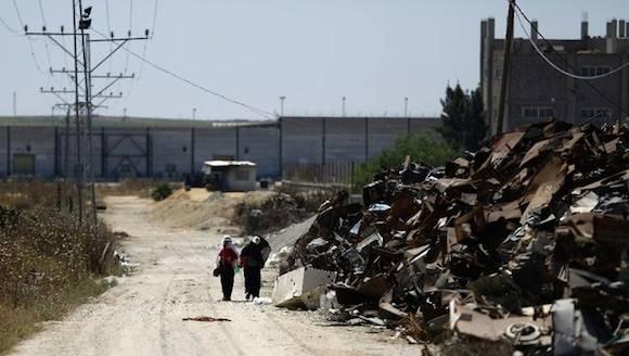 Mujeres palestinas caminan por las zonas donde se militantes de Hamas fueron localizados cerca de la frontera con Israel, al este de la ciudad de Gaza. Foto: Afp