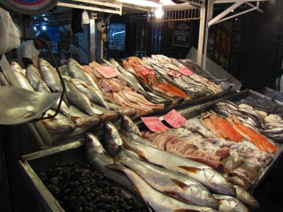 La foto muestra una modesta pescadería de Santiago de Chile, un día cualquiera, donde alguna carne de atractivo color naranja identifica al salmón.