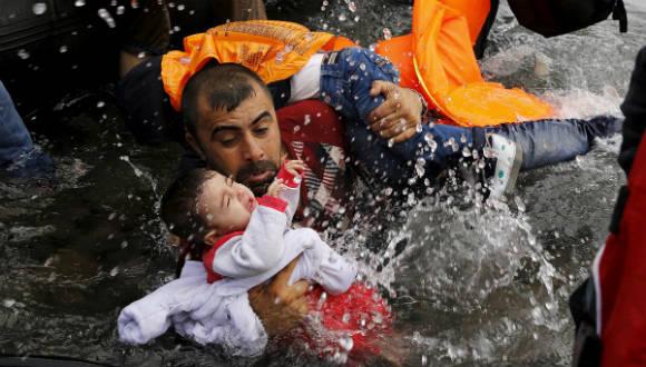 Un refugiado sirio coge a sus hijos mientras trata de salir de un bote en la isla griega de Lesbos, tras cruzar una parte del mar Egeo desde Turquía. Foto: Reuters.