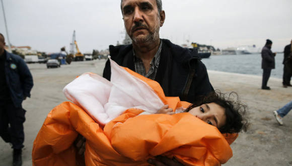 A su llegada al puerto de Mitilene en la isla griega de Lesbos, un refugiado sirio sostiene a su hija arropada con una manta, tras haber sido rescatados en pleno mar abierto.  Foto: Reuters