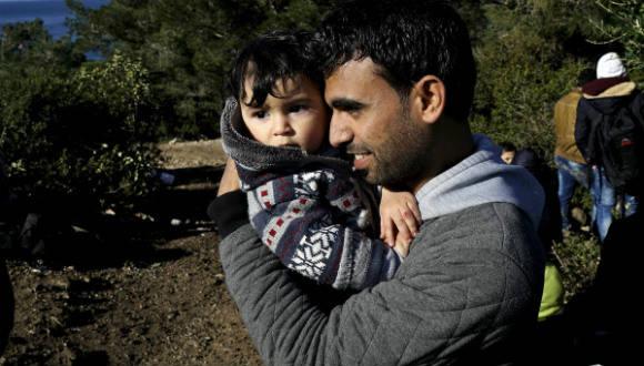 Un refugiado sirio abraza a su bebé mientras espera en un camino cercano a la costa en la ciudad de Dikili (Turquía), después de que los gendarmes turcos les impidieran zarpar hacia la isla de Lesbos. Foto: Reuters