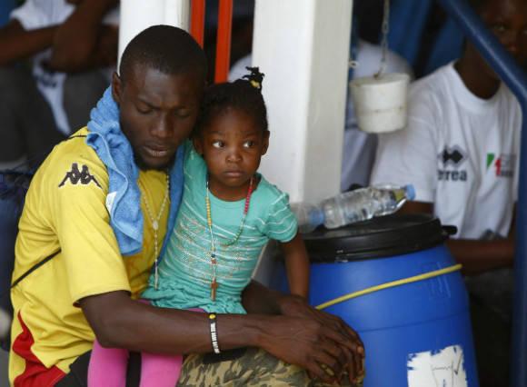 Un migrante subsahariano coge a su hija mientras esperan sentados sobre la cubierta del barco de rescate MV Phoenix en Vibo Valentia (Italia). Muchos refugiados tratan de cruzar a Italia vía Libia. Foto: Reuters