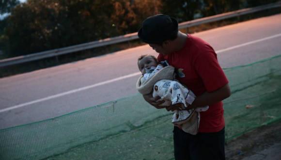 Un hombre espera con su bebé en otro campo de refugiados tras haber escapado de una evacuación forzosa en el campamento de Idomeni (Grecia). Foto: Getty Images