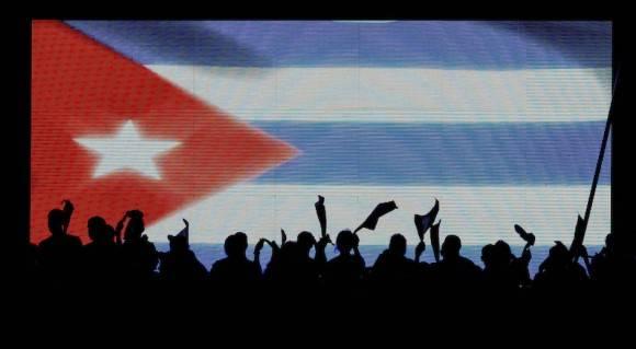 Jóvenes reflejados en una bandera gigante, antes del desfile del Primero de Mayo en la Plaza de la Revolución, en La Habana, Cuba, el domingo 1 de mayo de 2016. Foto: Ramón Espinosa/ AP