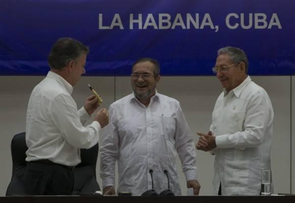 """Juan Manuel Santos le regala a Timochenko el """"balígrafo"""", elaborado con antiguas balas salidas del conflicto."""