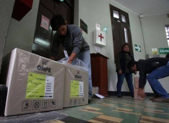 Funcionarios de la Oficina Nacional de Procesos Electorales (ONPE), entrega material electoral en el Colegio El Olivar, ubicado en San Isidro, en Lima. Foto: EFE.