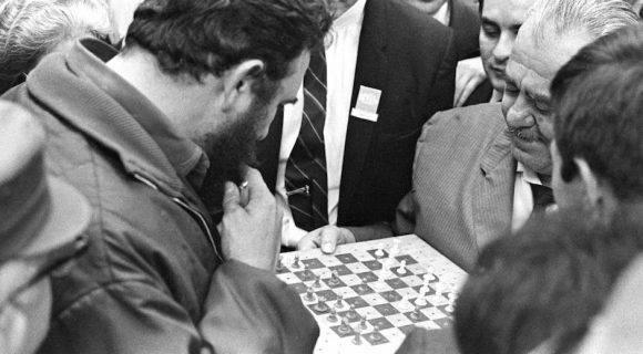 Fidel y Camarena. Con el tablero sujeto con la mano izquierda de ambos rivales, en posición de pie en medio del Salón de Embajadores del Habana Libre, se jugó esta partida. Justamente en el momento de tomar el peón dama para llevarlo a la casilla 3 Dama, se produjo una foto que ha sido muy divulgada.