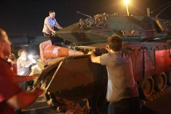 La gente intenta detener un tanque en las calles de Ankara.