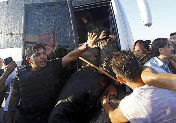 La policía protege a los golpistas de la multitud antes de ser detenido.