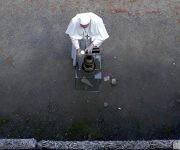 """El papa Francisco enciende una vela ante el """"muro de la muerte"""". Foto: EFE."""