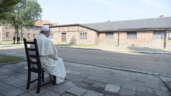 Francisco sentado frente a un barracón durante su visita al campo de concentración nazi de Auschwitz. Foto: EFE.