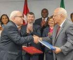 Ricardo Cabrisas y Mario Giro, intercambian los documentos de regulación de la deuda, tras su firma. Foto: José Manuel Correa/ Granma.