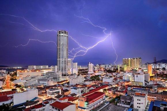 """""""Los rayos parecen dar en la torre Komtar, el ícono más destacado de George Town, capital del estado de Penang en Malasia. Simboliza el rejuvenecimiento que la ciudad, famosa por una mezcla única de edificios centenarios y estructuras modernas, ha experimentado en los últimos años. Aunque la mayor parte de sus barrios antiguos fueron descuidados en la década de 1990 y comienzos de la de 2000, su declaración como patrimonio mundial por la Unesco comenzó una transformación y, hoy, forman en su conjunto un concurrido destino turístico"""" – Jeremy Tan Jeremy Tan / National Geographic Travel Photographer of the Year Contest"""