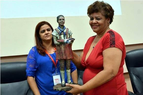 Olga Lidia Tapia recibe de manos de los pioneros un reconocimiento para Fidel Castro, la figura de una pionera de la etapa Moncadista, durante la clausura de la Asamblea Nacional Pioneril. Foto: ACN.