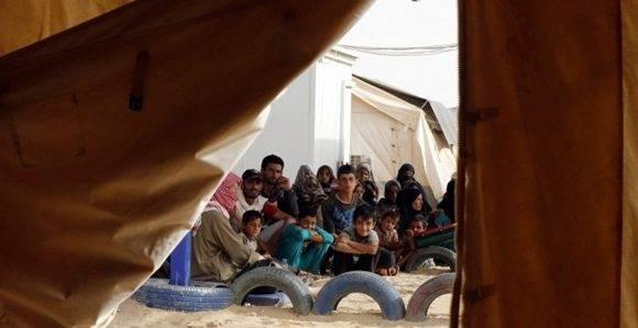 Refugiados sirios esperan para subir a un vehículo militar de Jordania tras conseguir cruzar la frontera norte entre ambos países con sus familias. REUTERS/