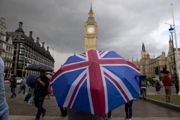 En una céntrica calle de Londres una persona sostiene un paraguas con la bandera británica. Foto: AFP.