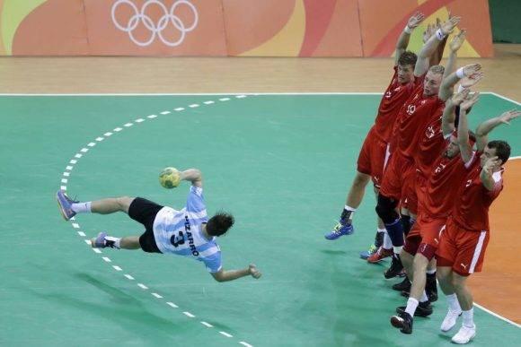 El argentino Federico Pizarro intenta marcar un penalti durante la preliminar masculina de handball entre Dinamarca y Argentina. Foto: Matthias Schrader/ AP.