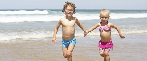 A little boy and girl, brother & sister, running together in the water at the beach, wearing swimmers, having fun.