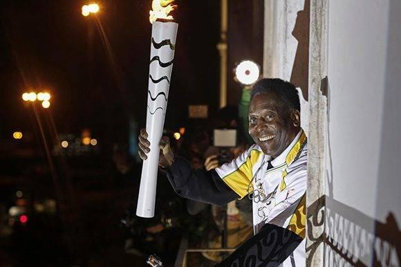 Pelé sostiene la antorcha olímpica. El astro del fútbol no estará en la inauguración por problemas de salud. Foto: AFP PHOTO/ Andre Luiz Mello.