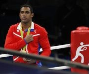 Cuba's Arlen Lopez sings the national anthem as the Cuban flag is raised after winning his gold medal for the men's middleweight 75-kg boxing at the 2016 Summer Olympics in Rio de Janeiro, Brazil, Saturday, Aug. 20, 2016. (AP Photo/Vincent Thian)
