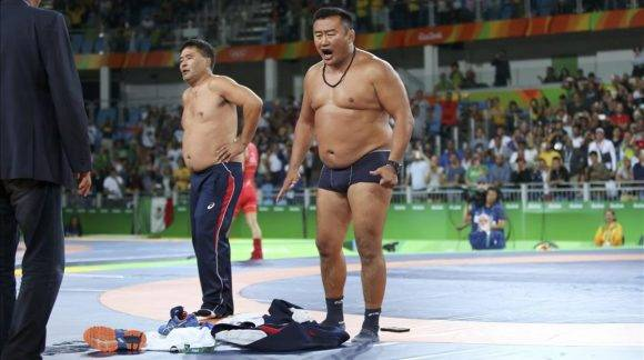 2016 Rio Olympics - Wrestling - Final - Men s Freestyle 65 kg Bronze - Carioca Arena 2 - Rio de Janeiro Brazil - 21 08 2016 The coach of Mandakhnaran Ganzorig MGL of Mongolia stands undressed as he protests after the match against Ikhtiyor Navruzov UZB of Uzbekistan REUTERS Toru Hanai FOR EDITORIAL USE ONLY NOT FOR SALE FOR MARKETING OR ADVERTISING CAMPAIGNS