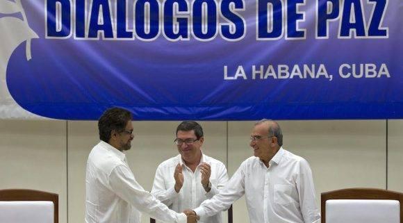 Humberto de la Calle, derecha, estrecha la mano Ivan Marquez, ante los aplausos del Canciller cubano Bruno Rodriguez . Foto: Ramon Espinosa/ AP